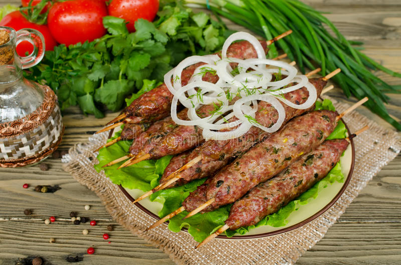 Grilled kebabs on wooden skewers and fresh vegetables stock photo