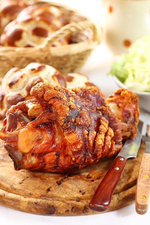 Grilled knuckle of pork. With bread rolls and lettuce salad stock images