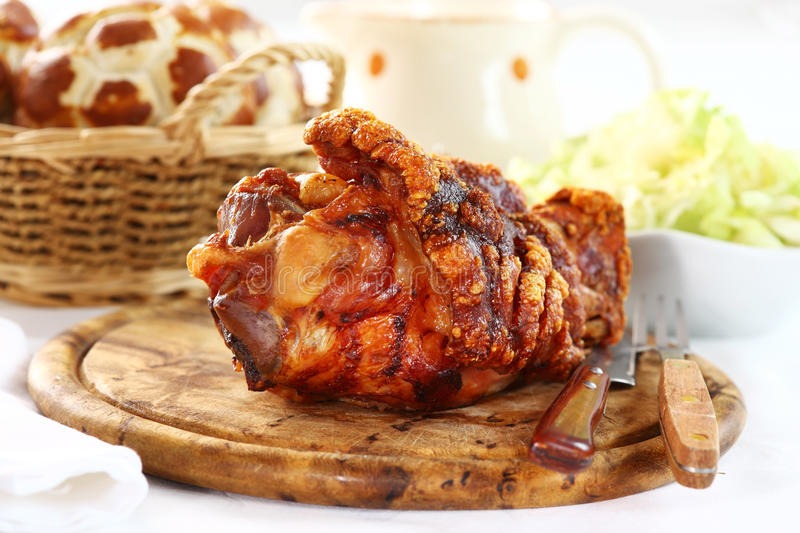 Grilled knuckle of pork. With bread rolls and lettuce salad royalty free stock image