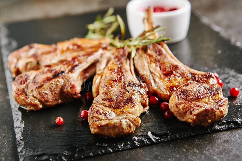 Grilled Lamb Chops with Cranberries and Rosemary. On Natural Black Stone Background. Roasted Cutlets on Creative Restaurant Backdrop. Mutton Ribs with Spices royalty free stock image