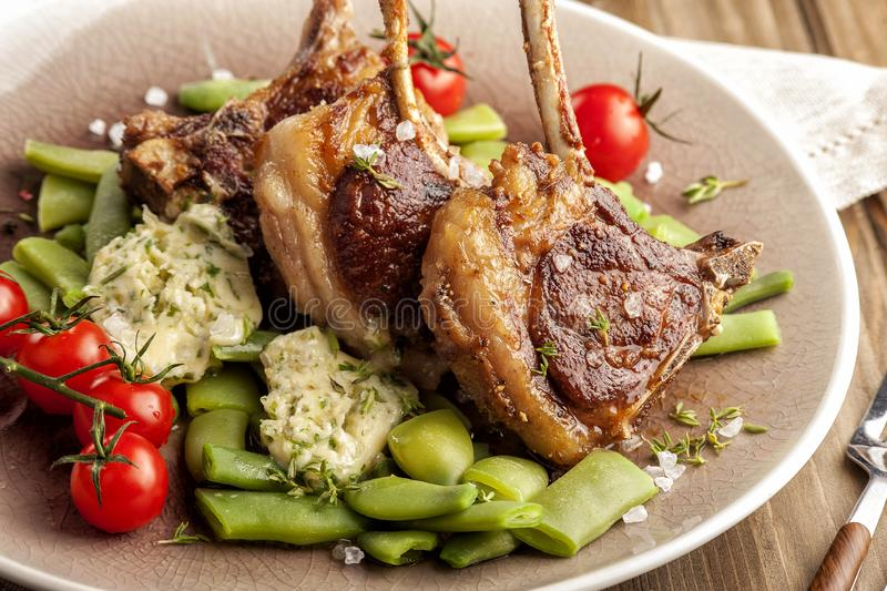 Grilled lamb chops with a garnish of green beans and fragrant butter. royalty free stock images
