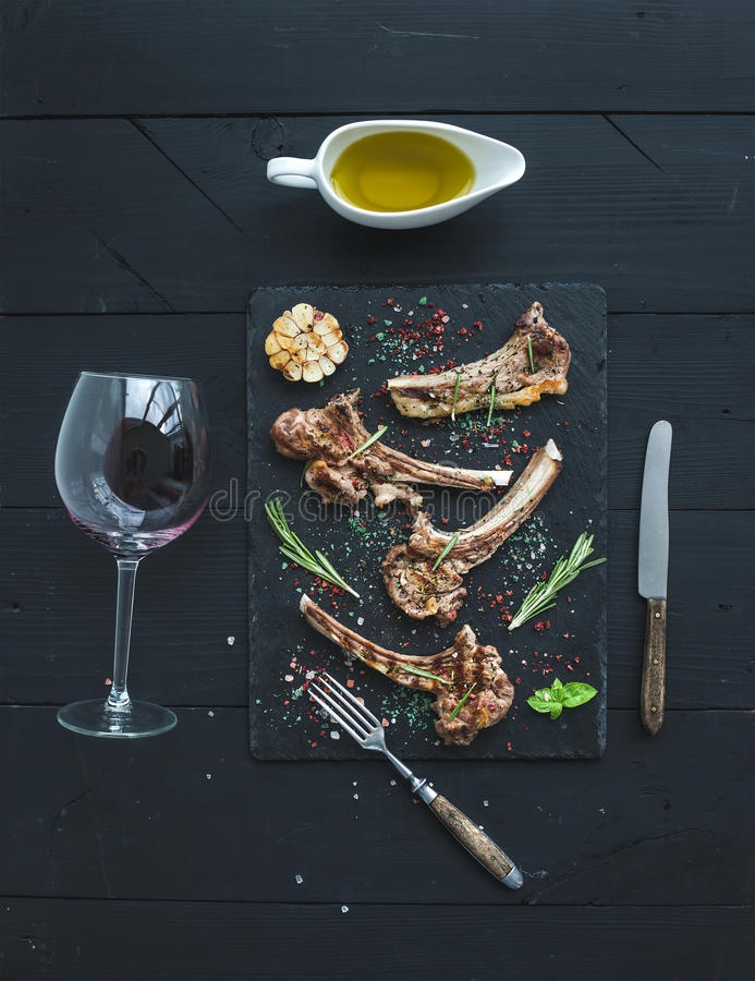 Grilled lamb chops. Rack of Lamb with garlic, rosemary, spices on slate tray, wine glass, oil in a saucer over black royalty free stock image