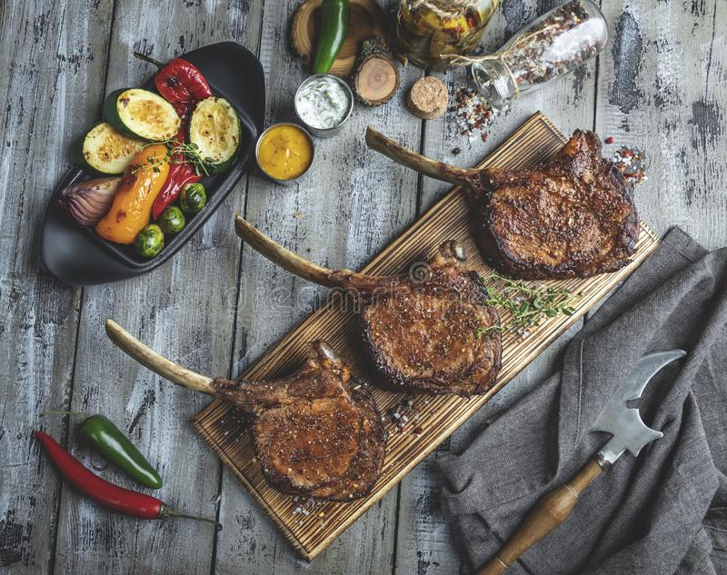 Grilled lamb,mutton meat chops with vegetables on a serving board. Rustic food concept.  stock photography
