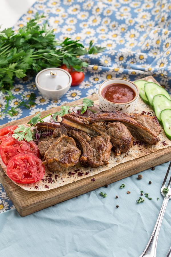 Grilled lamb ribs on cutting board with fresh vegetables and tomato sauce on fabric background stock photo