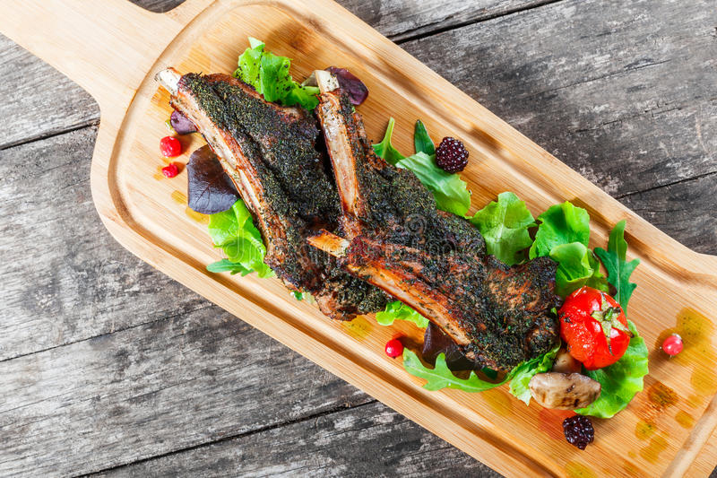 Grilled lamb ribs in herbs and greens, fresh salad, grilled vegetables and berries on cutting board on wooden background stock image