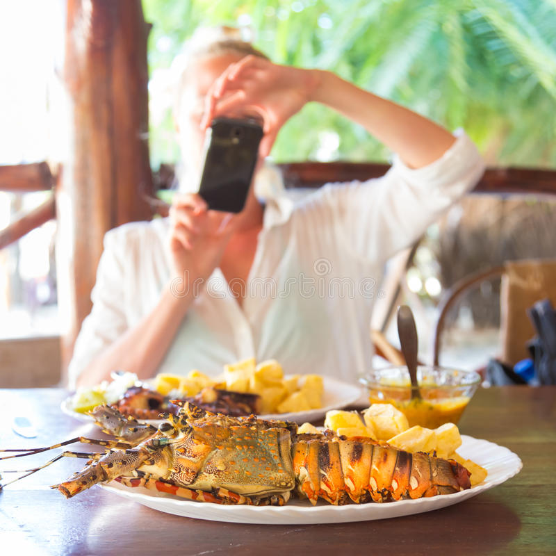 Grilled lobster served with potatoes and coconut sauce. Foodie blogger on tropical vacations using mobile phone to take photo of a plate of grilled lobster royalty free stock photos