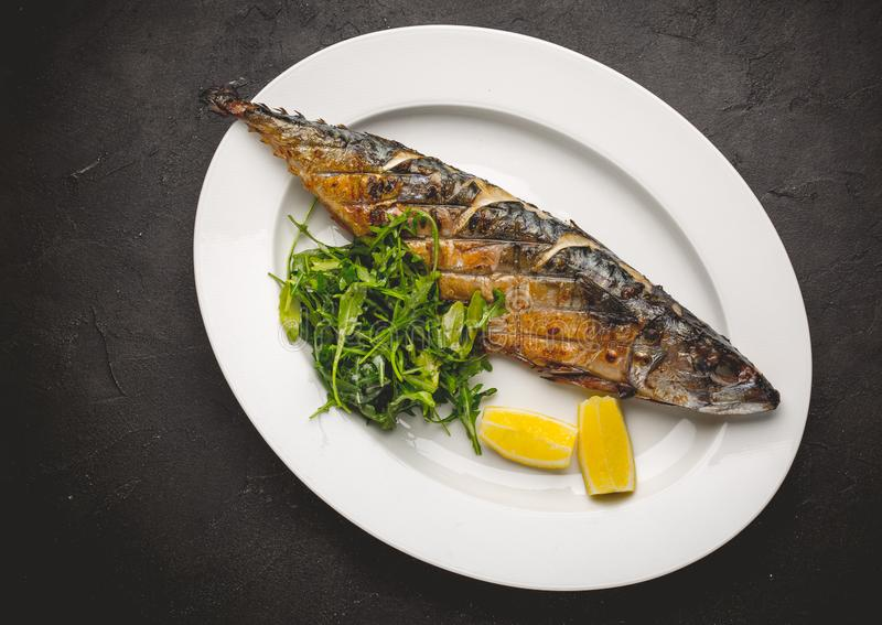Grilled mackerel fillets with lemon on black board stock photo