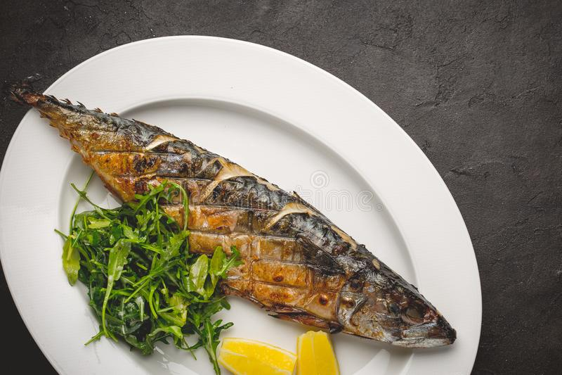 Grilled mackerel fillets with lemon on black board royalty free stock image