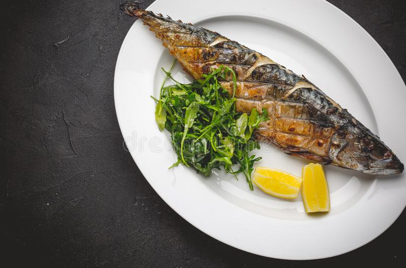 Grilled mackerel fillets with lemon on black board royalty free stock photo