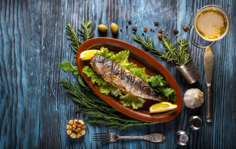 Grilled mackerel fillets with lemon on rustic background stock photography