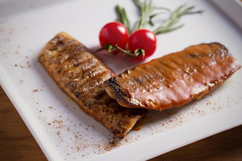 Grilled mackerel fish fillet in tomato mustard sauce, served with cherry tomatoes, rosemary and lemon stock photography