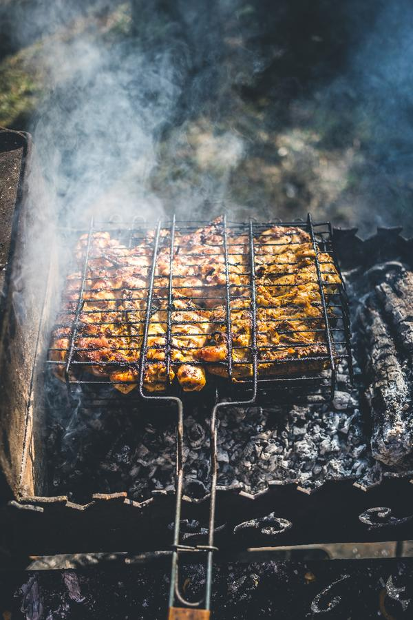 Grilled marinated chicken on a metal grid.  royalty free stock image