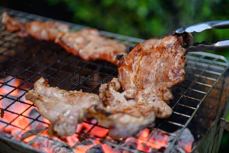 Grilled marinerade griskött på kolgaller i matställe arkivfoto