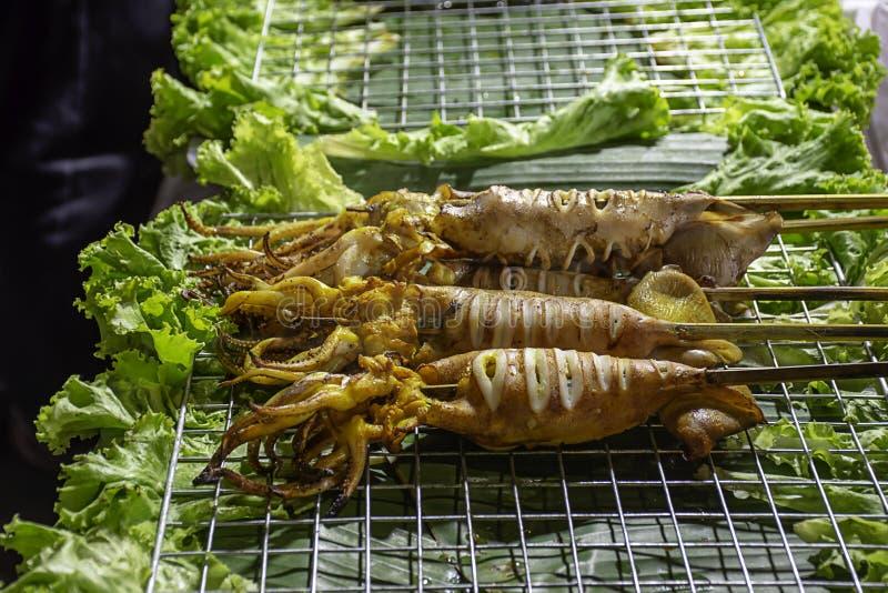 Grilled marinerade tioarmade bläckfisken med havs- sås och grönsaker på stålskyddsgallrarna med värmen fotografering för bildbyråer
