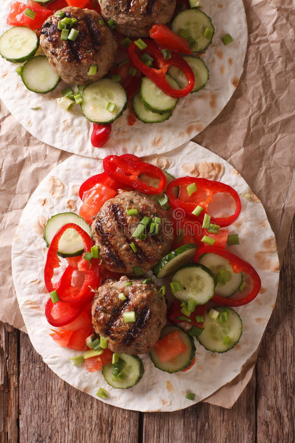 Grilled meat balls with fresh vegetables on a flat bread close u stock photo