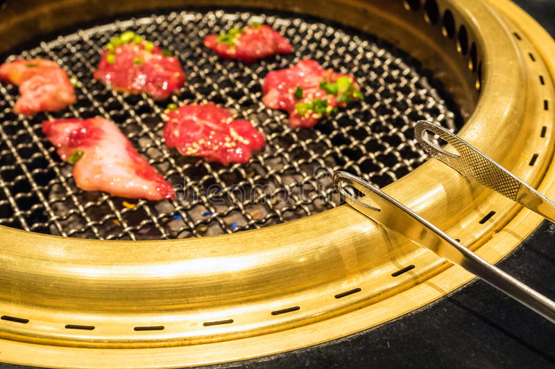 Grilled meat. In Korean or Japanese style selective focus on tongs stock photography