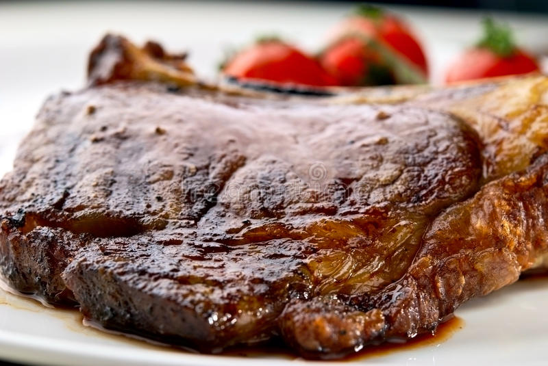 Grilled meat ribs on white plate with tomatoes stock photography