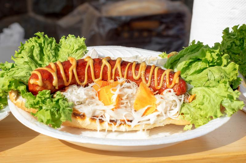 Grilled meat sausage. Asia Street Food Market. Grilled meat sausage decorated by mustard, with vegetable, cabbage, carrot and leaves of green lettuce, and stock photos