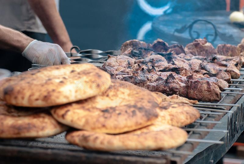 Shish kebab and pita bread on the grill in the smoke, close-up stock image