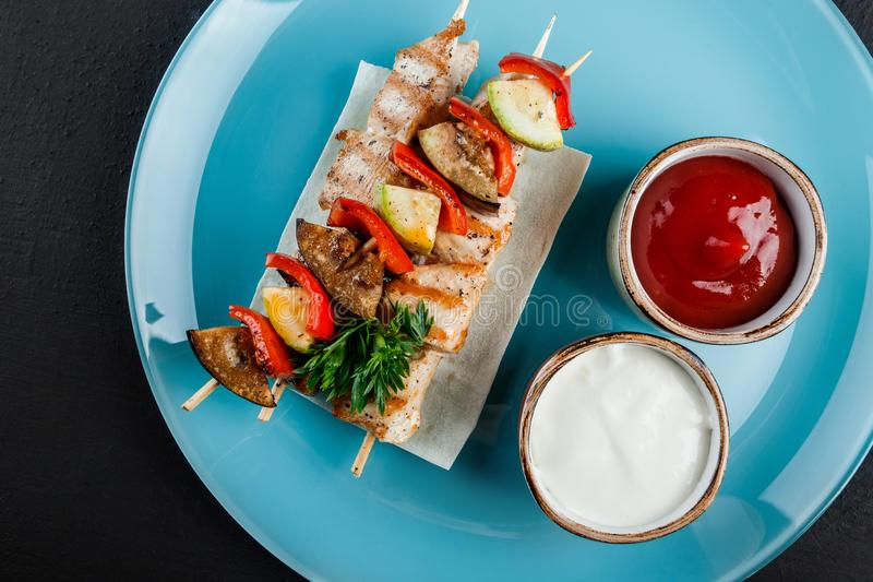 Grilled meat shish and vegetables kebab on skewers with sauce in plate over dark background. Healthy food. Hot meat dishes, stock image