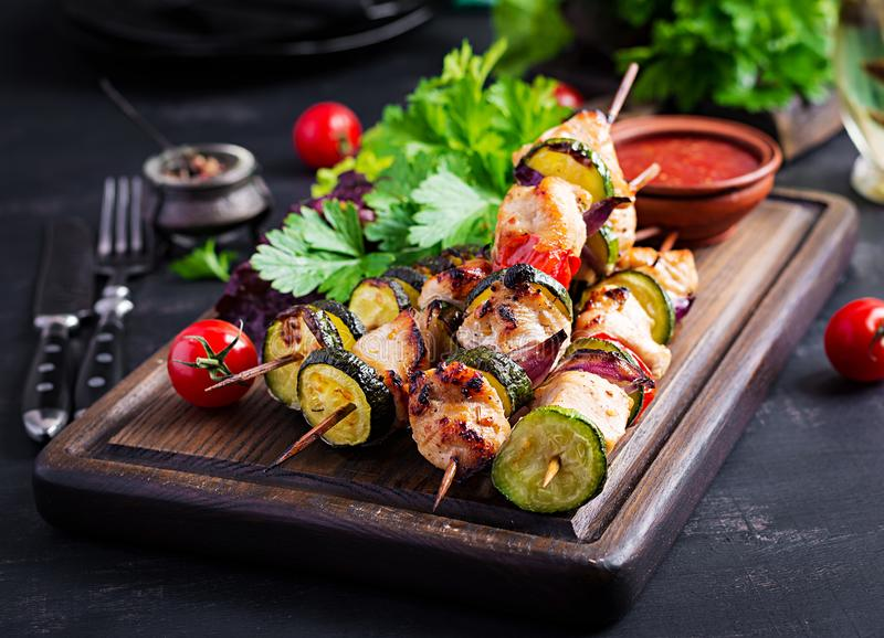 Grilled meat skewers, chicken shish kebab with zucchini, tomatoes and red onions. Grilled meat skewers, chicken  shish kebab with zucchini, tomatoes and red royalty free stock photography
