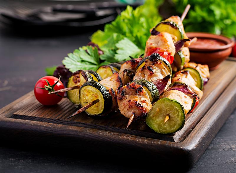 Grilled meat skewers, chicken shish kebab with zucchini, tomatoes and red onions. Grilled meat skewers, chicken  shish kebab with zucchini, tomatoes and red royalty free stock images