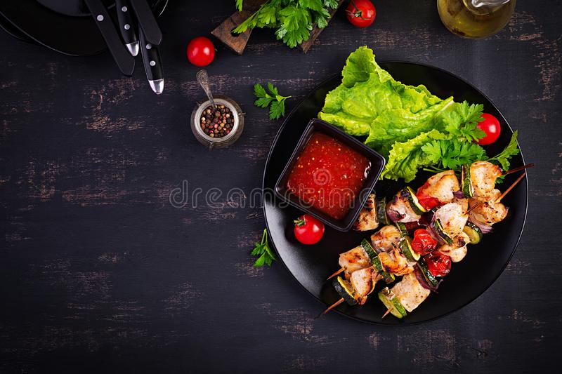 Grilled meat skewers, chicken  shish kebab with zucchini, tomatoes and red onions. Barbecue food. Top view stock image