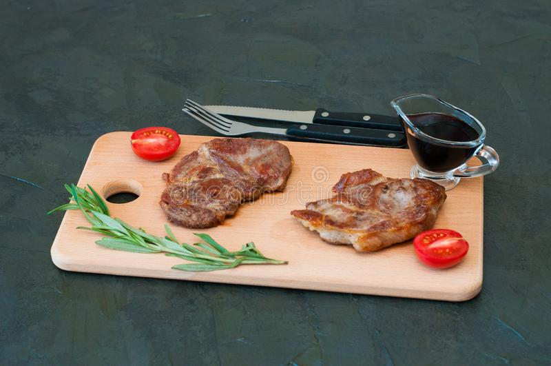 Grilled meat steaks of pork, veal or beef, with rosemary, soy sauce and tomato on cutting board, fork and knife royalty free stock photo