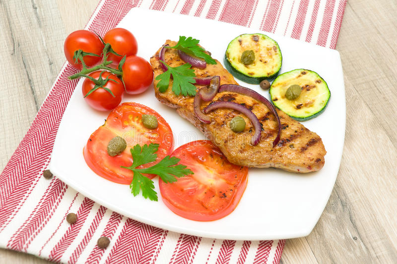 Grilled meat with vegetables on a plate. horizontal photo. Appetizing meat grilled with vegetables on a plate. top view - horizontal photo stock photos