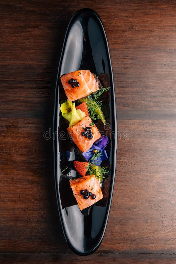 Grilled Medium Rare Salmon Cube topping with caviar and served with strawberry and orange in black plate royalty free stock photos