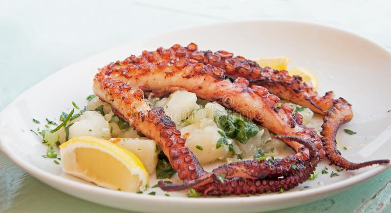 Grilled octopus on a plate with potato and lemon stock photography