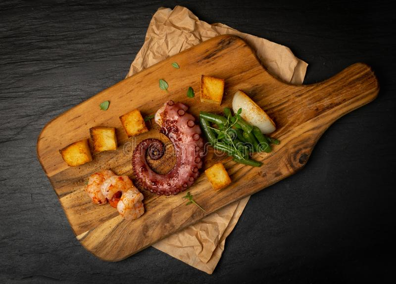 Grilled octopus tentacle on a wooden cut board served with shrimps royalty free stock photography