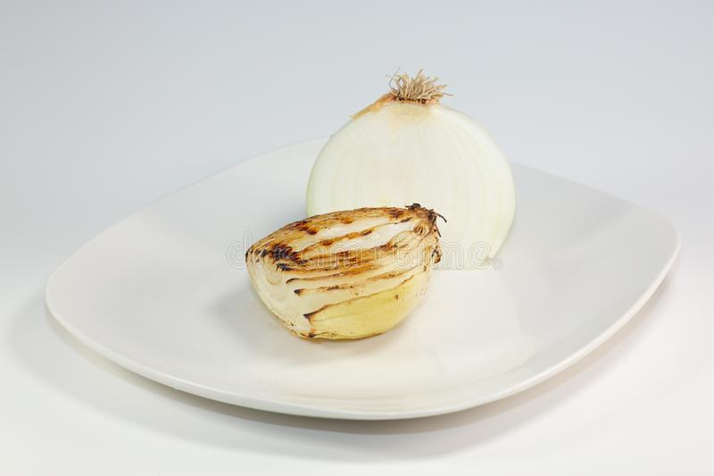 Grilled onion freshly removed from the grilled and placed on a white plate on the table royalty free stock images