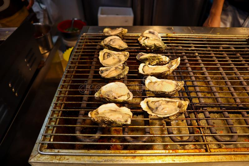 Grilled oysters as street food in Shanghai royalty free stock photography