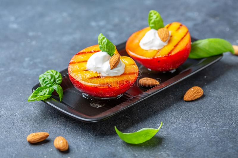 Grilled peach with honey, yogurt and almonds. Grilled peaches with honey, yogurt, almonds and fresh basil in a black plate on a grey textured background royalty free stock photography