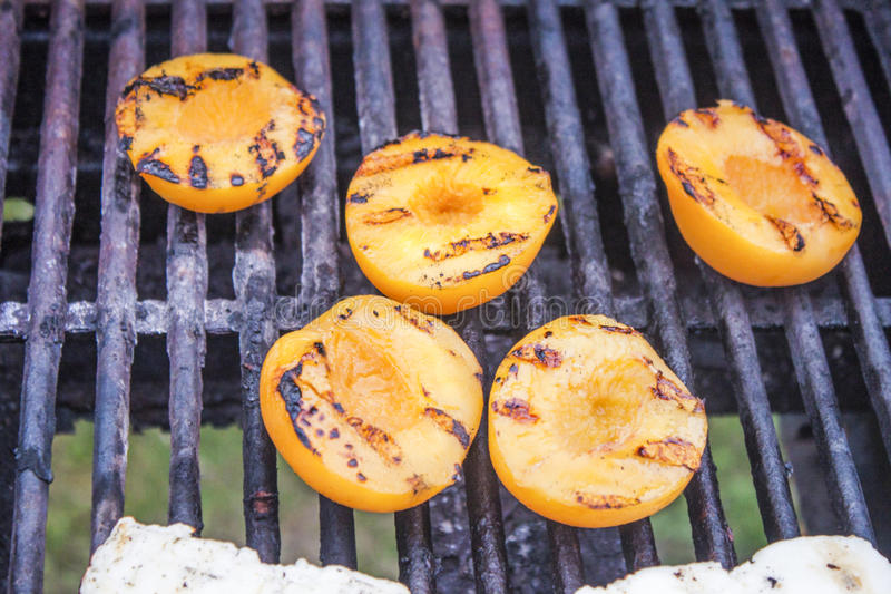 Grilled peaches. A lot of grilled peaches. on a barbeque royalty free stock images