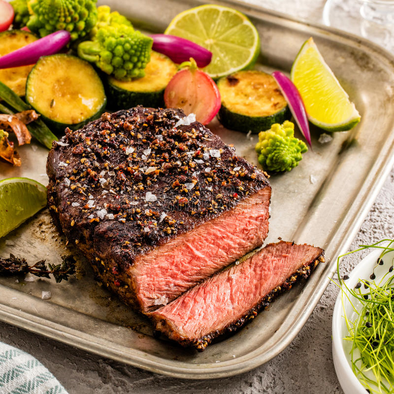 A grilled pepper steak garnished with lemon, onion and fresh her stock image