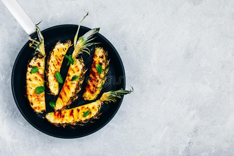 Grilled pineapple with fresh mint in cast iron pan on gray stone background royalty free stock photo