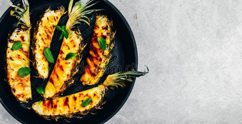 Grilled pineapple with fresh mint in cast iron pan on gray stone background stock photo