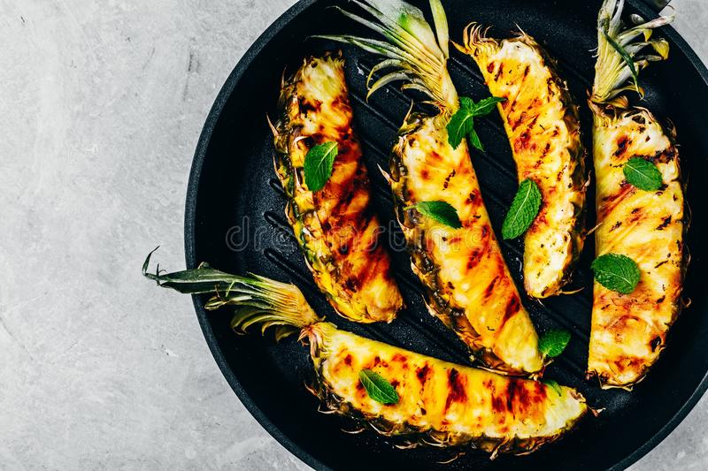 Grilled pineapple with fresh mint in cast iron pan on gray stone background royalty free stock image