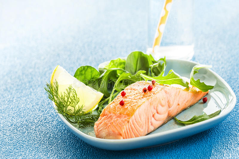 Grilled pink salmon steak with green salad. Grilled pink salmon steak served with green salad, dill and a lemon wedge for seasoning on a textured blue background stock image