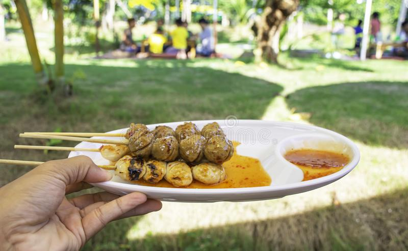 Grilled pork and beef meatballs with seafood sauce on white plastic plate in hand Background blurry Tourists on the lawn royalty free stock images