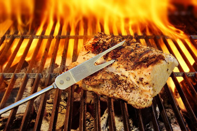 Grilled pork brisket. And flaming grill in background stock photo