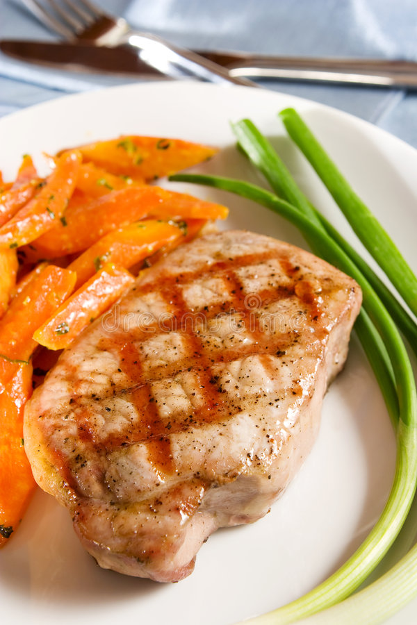 Grilled pork chop. With orange glaze carrot and spring onion stock image