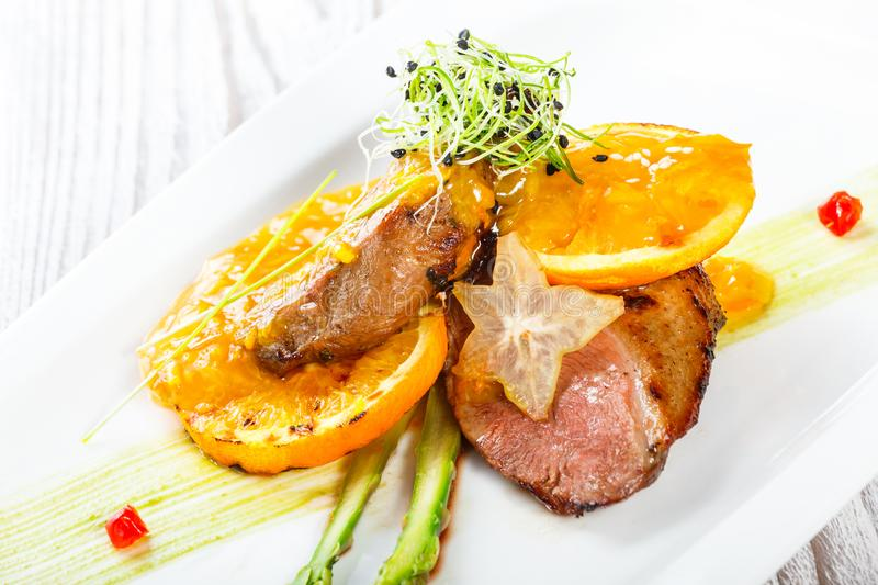 Grilled pork chop steak chargrilled to medium rare with orange sauce on wooden background stock image