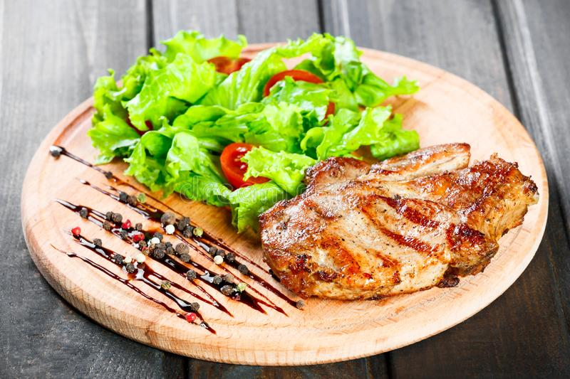 Grilled pork chop steak with fresh vegetable salad, tomatoes and sauce on wooden cutting board. Hot Meat Dishes royalty free stock images