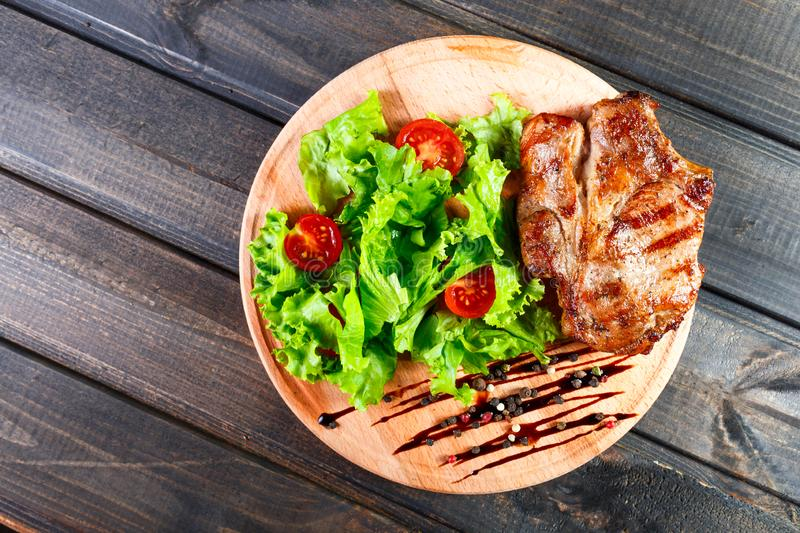 Grilled pork chop steak with fresh vegetable salad, tomatoes and sauce on wooden cutting board. Hot Meat Dishes. Top view, flat lay royalty free stock photo