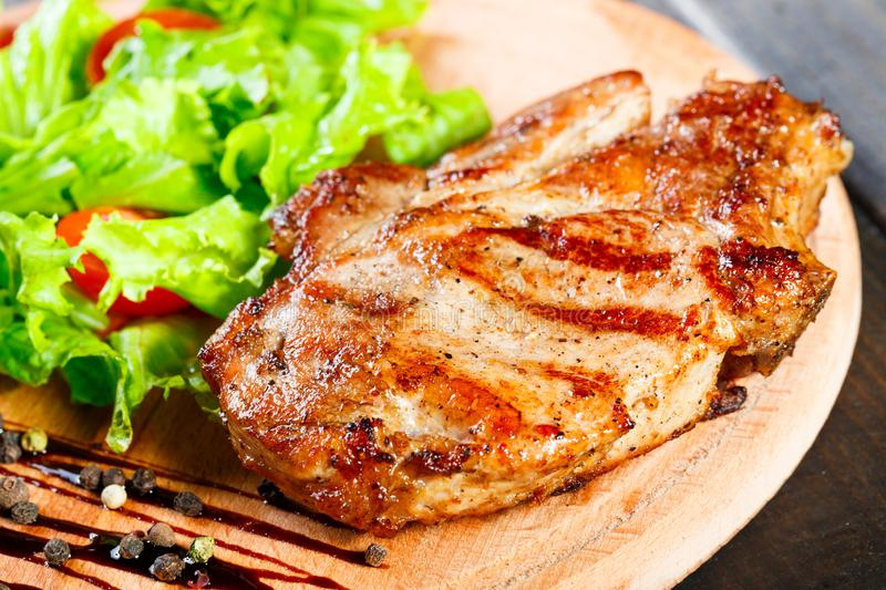 Grilled pork chop steak with fresh vegetable salad, tomatoes and sauce on wooden cutting board. Hot Meat Dishes. Top view, flat lay stock photos