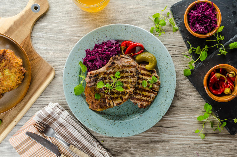 Grilled pork chops with herbs and garlic, potato pancakes stock image
