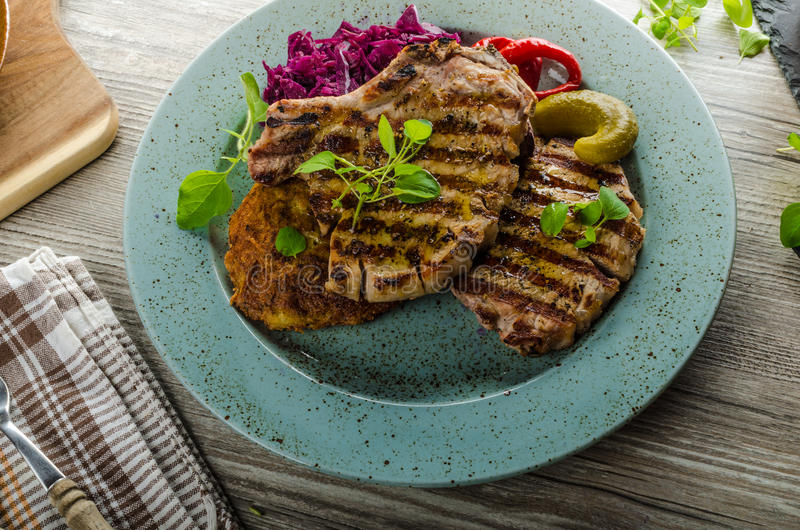 Grilled pork chops with herbs and garlic, potato pancakes royalty free stock image